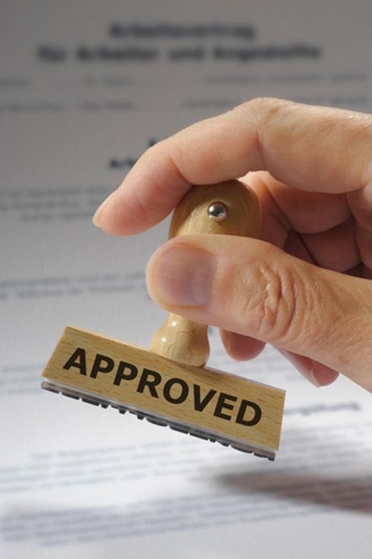Approval stamp held above documentation