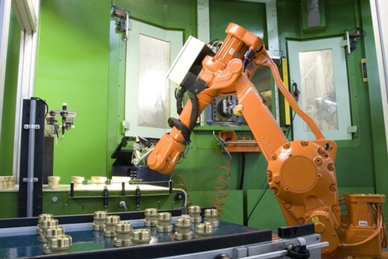 A robotic arm mills parts.