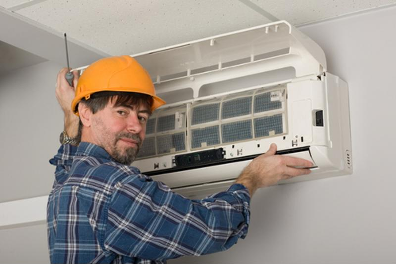A service technician reviews an air conditioning unit.