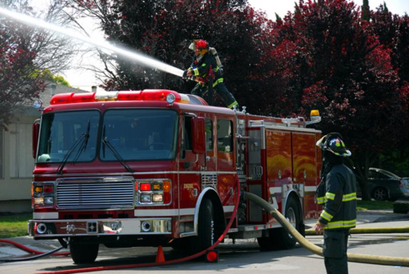 Fire engine and personnel at the scene of a residential fire.