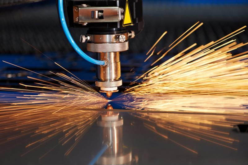 An industrial laser cuts sheet metal.