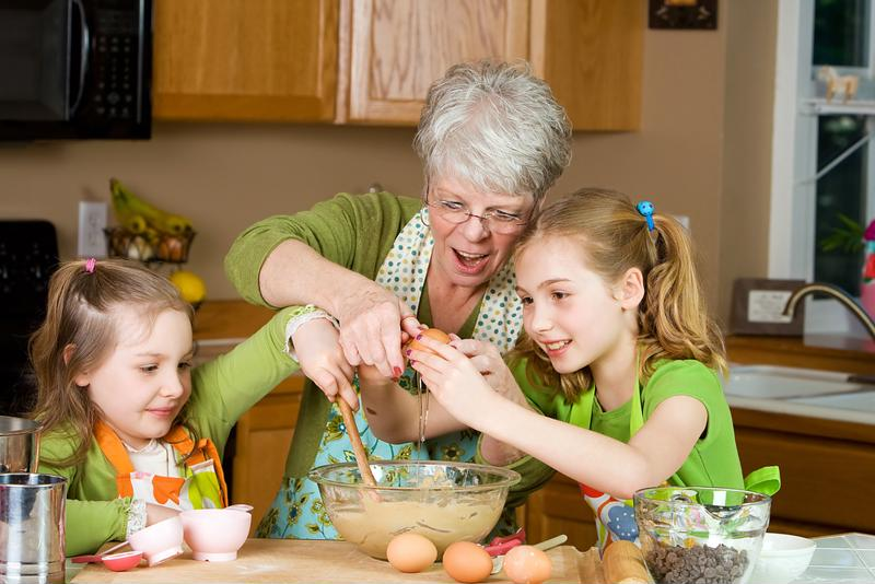 A grandma bakes with her granddaughters.