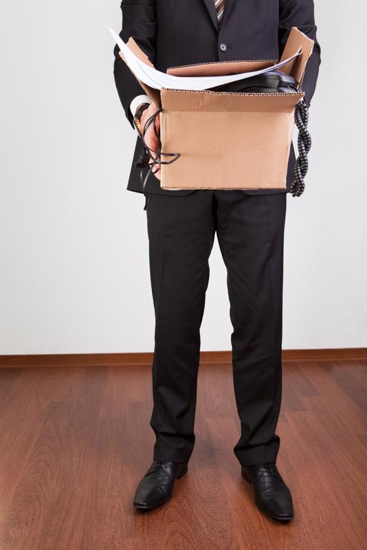 Laid-off employee holding a box of personal items.