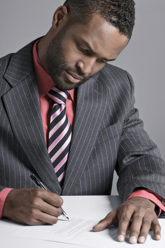 Man in suit filling out paperwork.