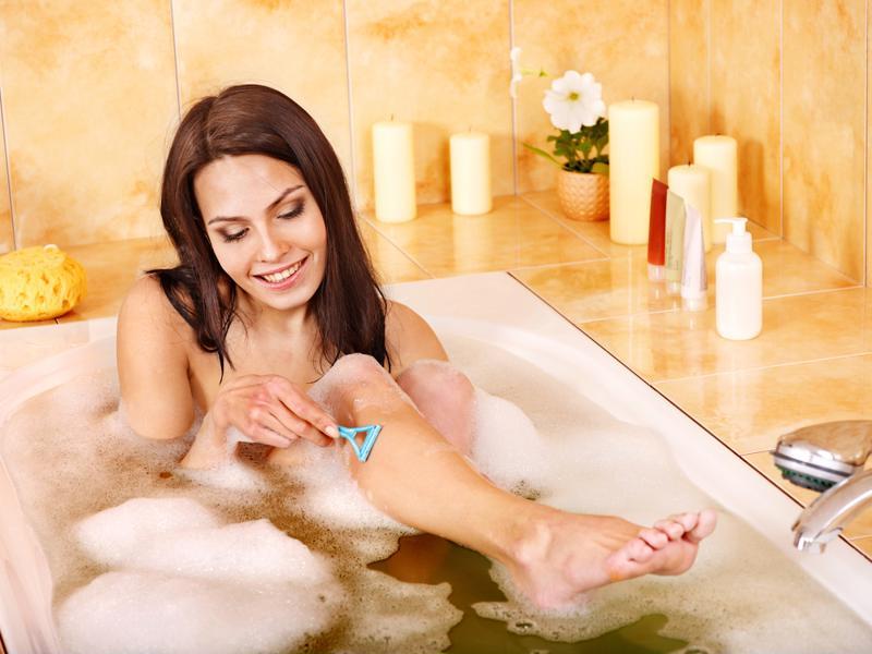 A woman shaving in the bathtub.