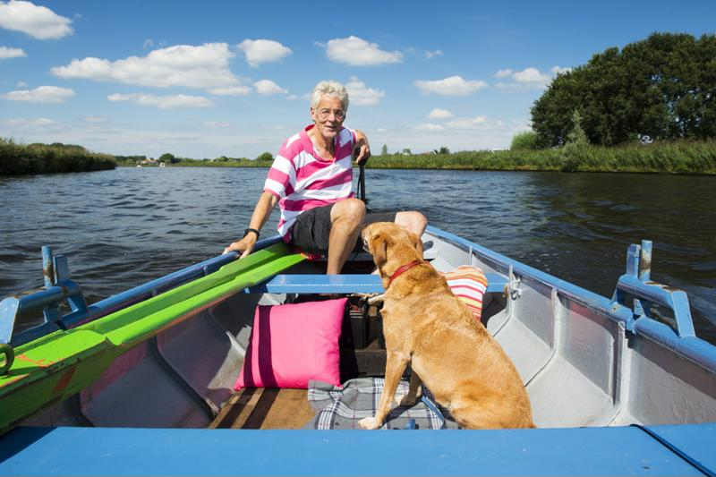 Woman on recreational boat with Golden retriever.
