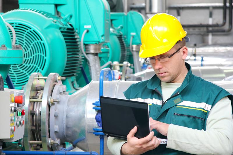 Manufacturing worker checks diagnostics on a laptop.