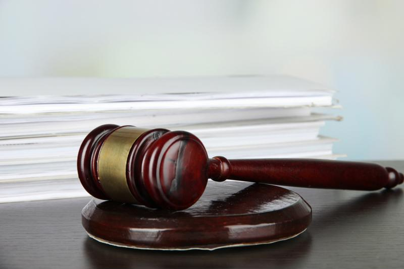 A gavel in front of a stack of legal documents.