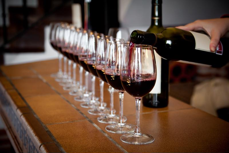 Glasses of red wine lined up for a wine tasting event.