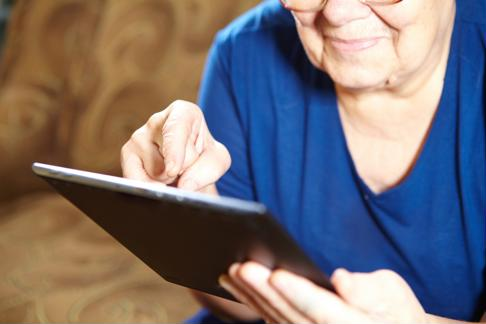Senior woman uses mobile tablet.