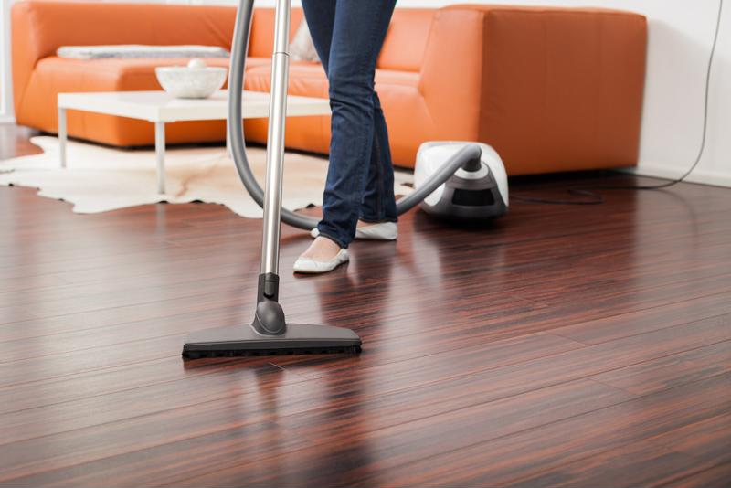 A woman vacuums a hardwood floor.