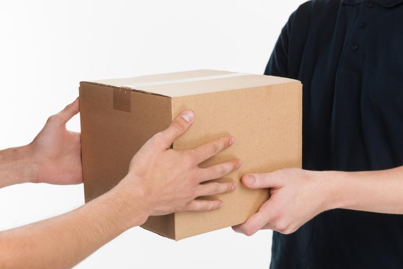 A delivery person hands over a package.