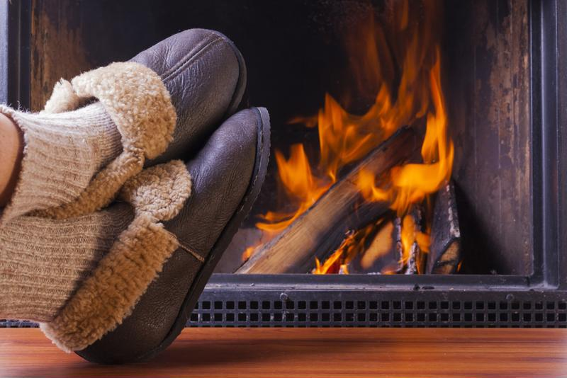 A person relaxes next to a realistic looking gas fireplace.