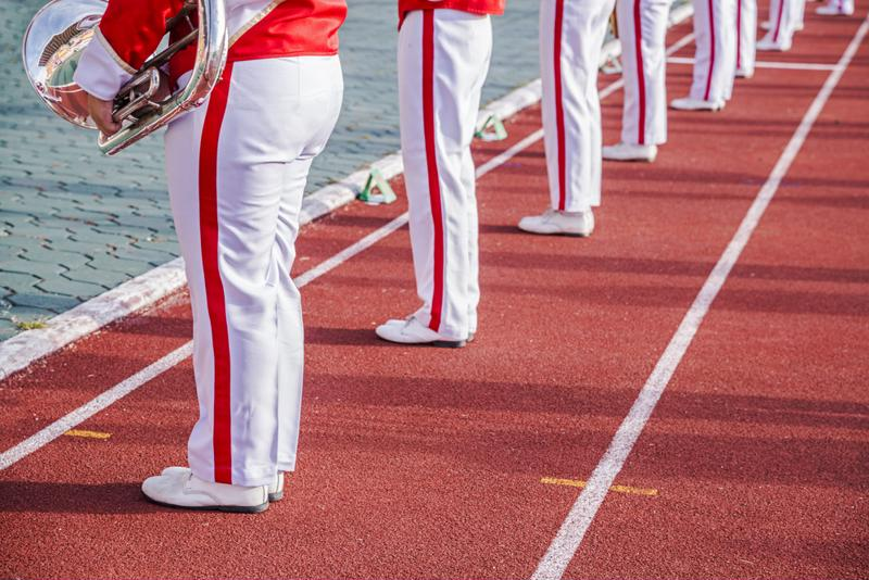 Marching band lines up on athletic track.