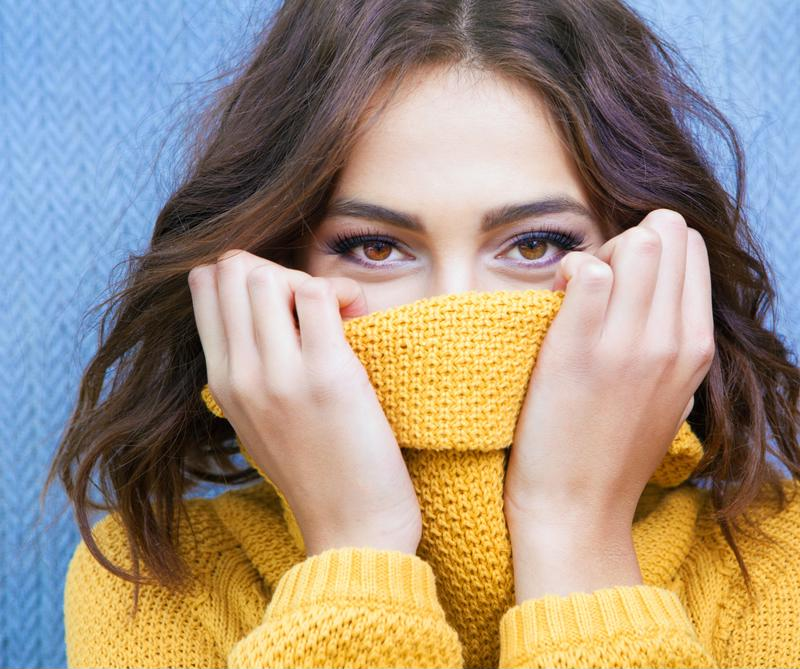 Woman hiding her face with a sweater.