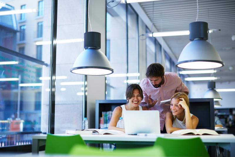 Happy employees talking in an office setting.