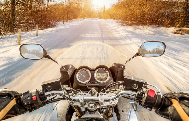 motorcycle riding down snowy road
