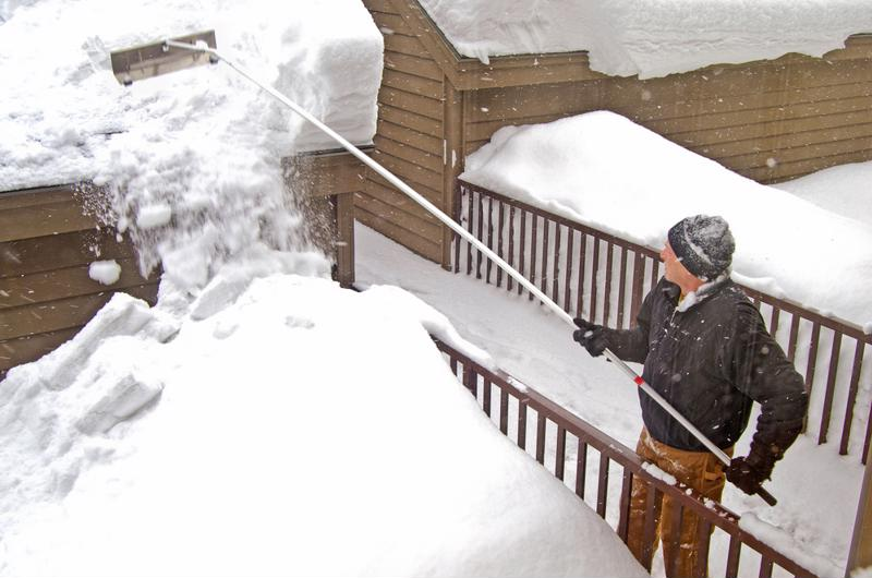 Man removing snow pile from roof with a snow rake.