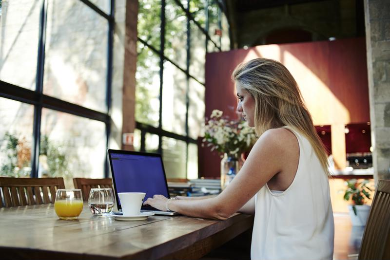 Female employee using a laptop to work remotely.