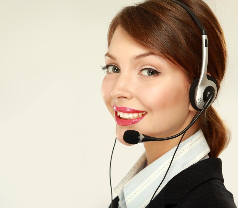 Customer service representative smiling, using headset.