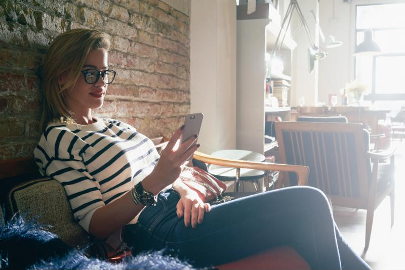 Woman using a smartphone while sitting on a couch.