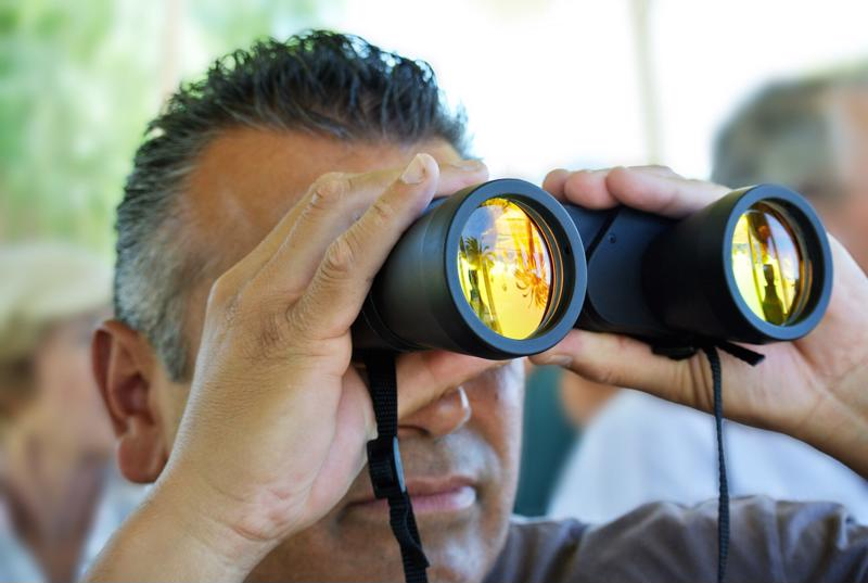 A man looks into the distance using binoculars.