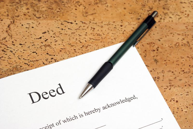 A home deed and pen.