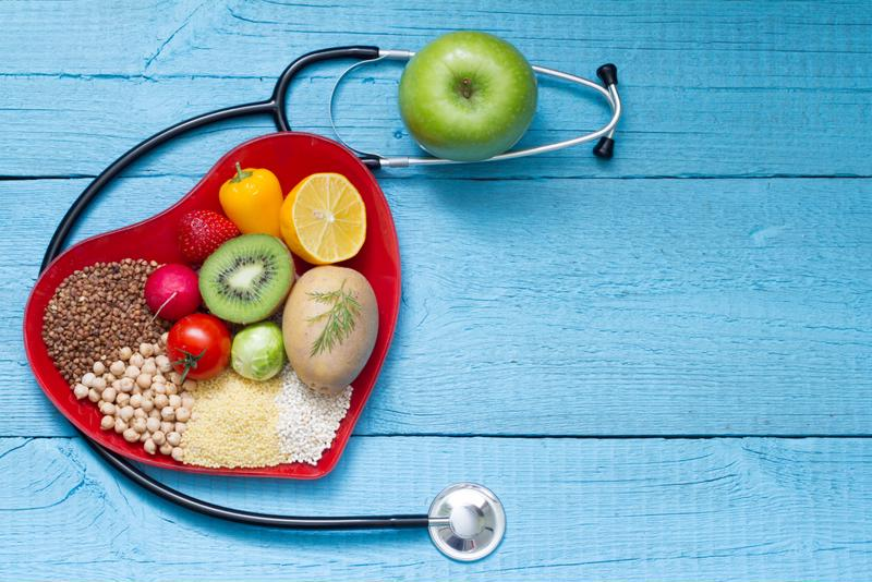 Fruits arranged in a heart shape next to a stethoscope