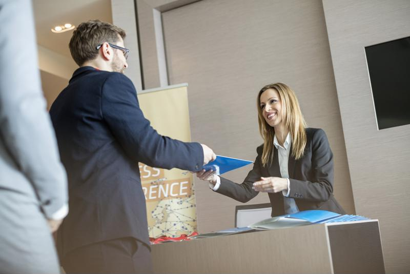 Executive hands a file to a receptionist.
