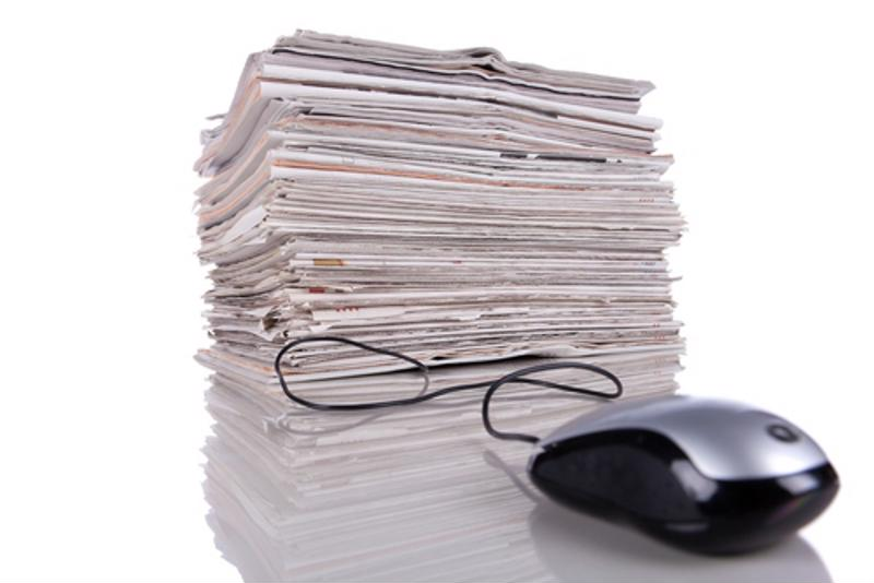 A computer mouse connected to a stack of papers.